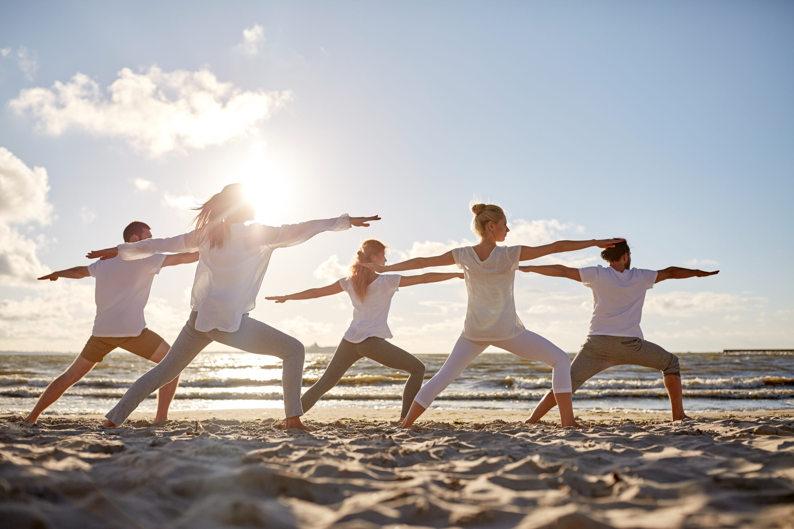 group of people doing therapeutic exercises on the beach
