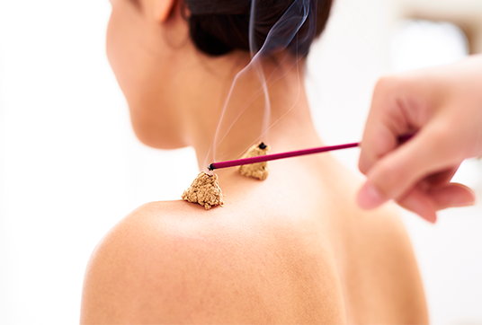 burning moxa with an incense stick